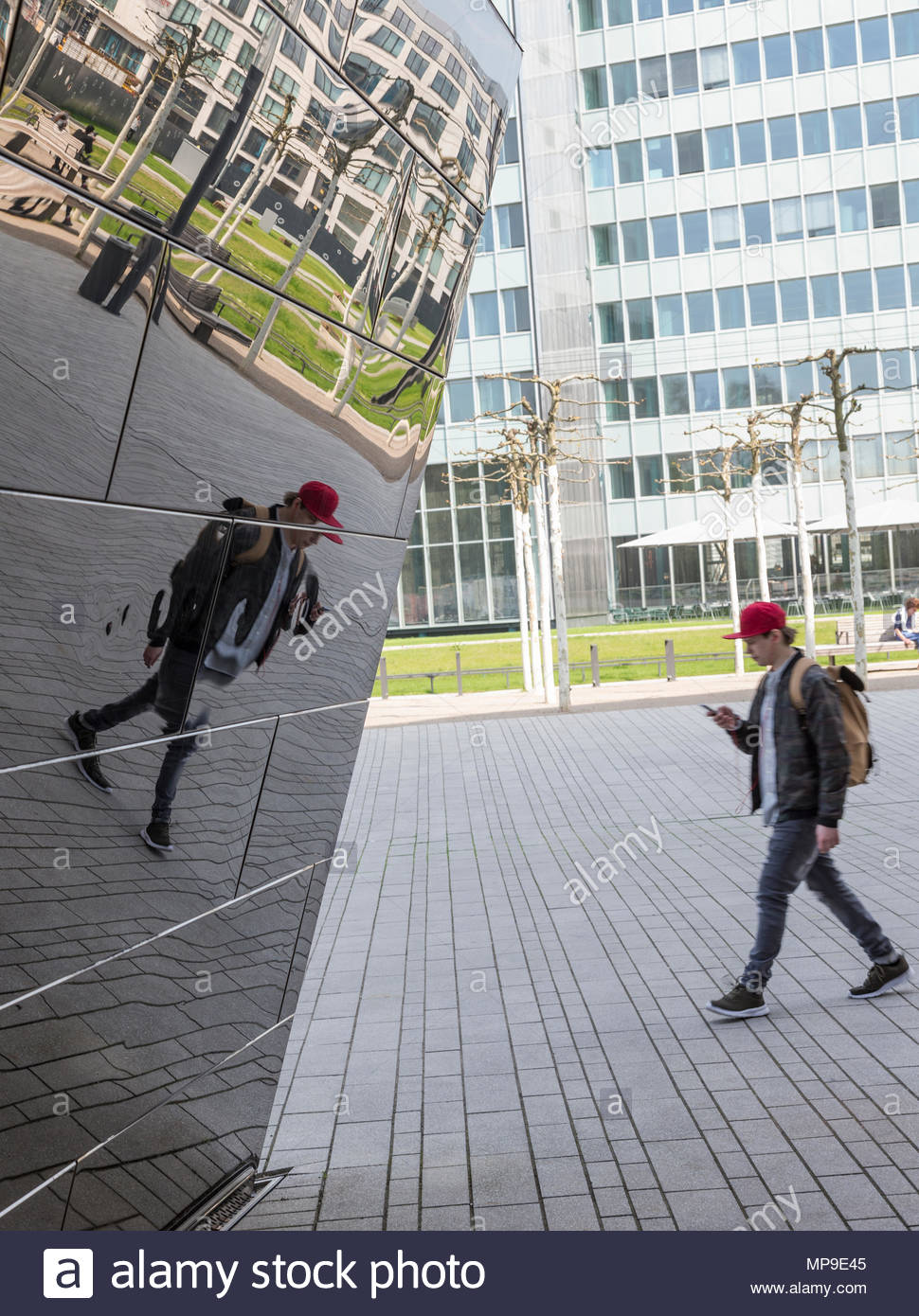 young man 20ish looking at his smart phone in thought absorbed oblivious of surrounding in step with mirror reflexion backpack casual wear red cap - Stock Image
