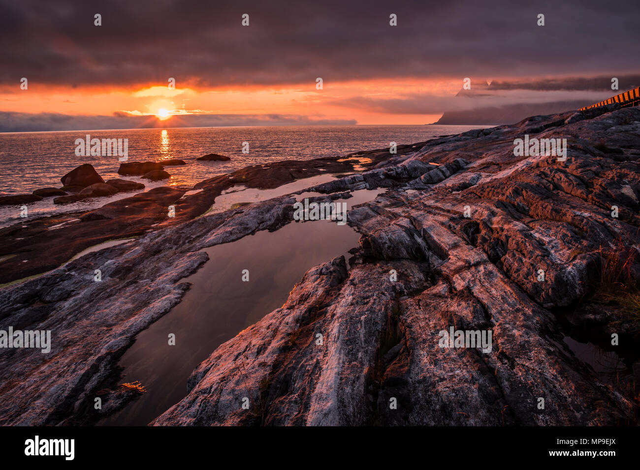 Dramatic, red and orange fiery summer sunset over the rocky shore with water puddles. Taken on island Senja, Norway. - Stock Image