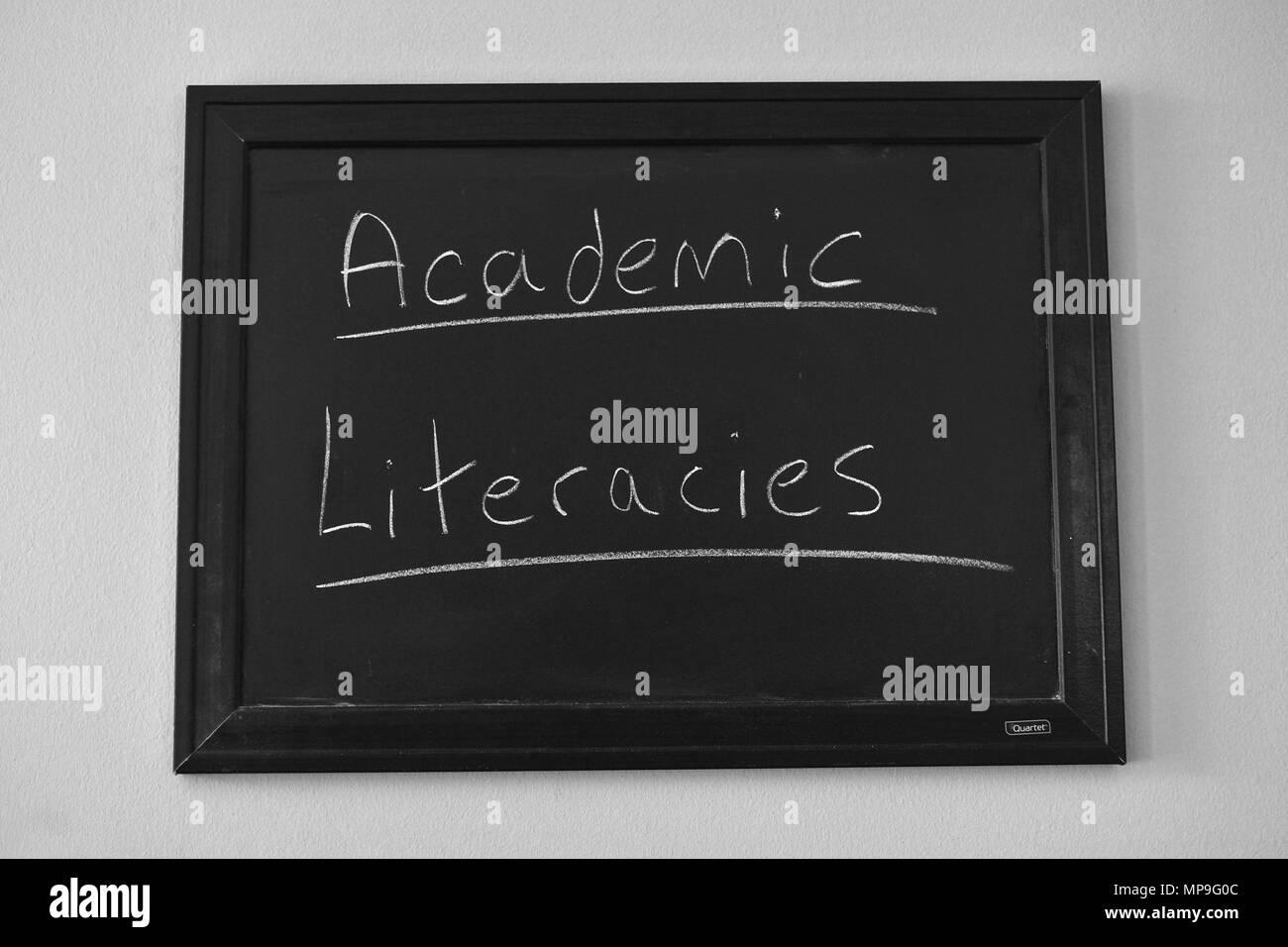 Academic Literacies written in white chalk on a wall mounted blackboard. - Stock Image