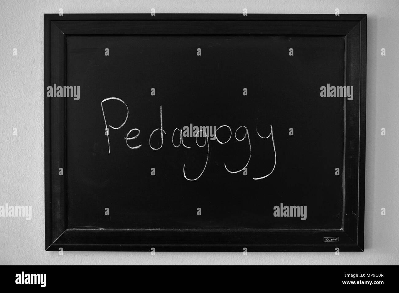 Pedagogy written in white chalk on a wall mounted blackboard. - Stock Image