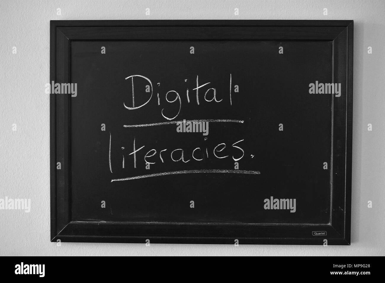 Digital literacies written in white chalk on a wall mounted blackboard. - Stock Image