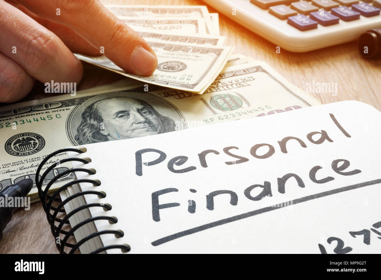Personal Finance written in a note and money. - Stock Image