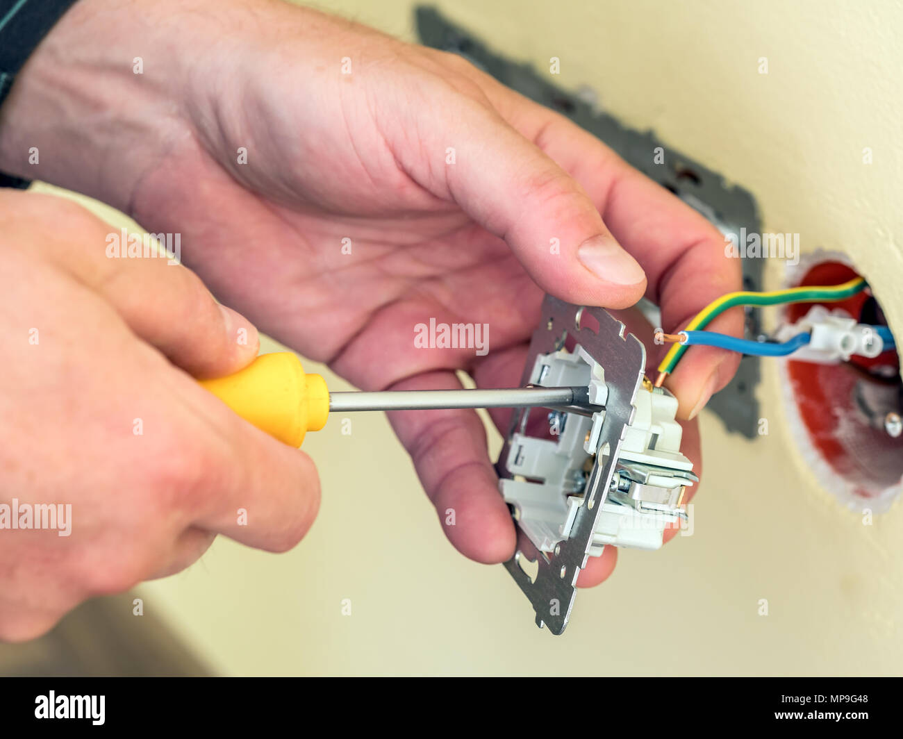 Closeup of electrician's hands installing wall socket Stock Photo