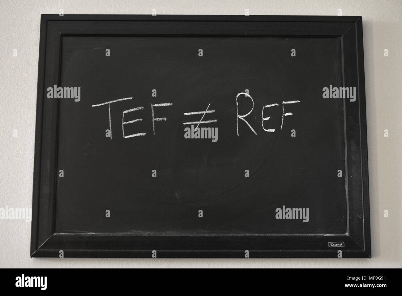 TEF ≠ REF written in white chalk on a black board mounted on a wall. - Stock Image