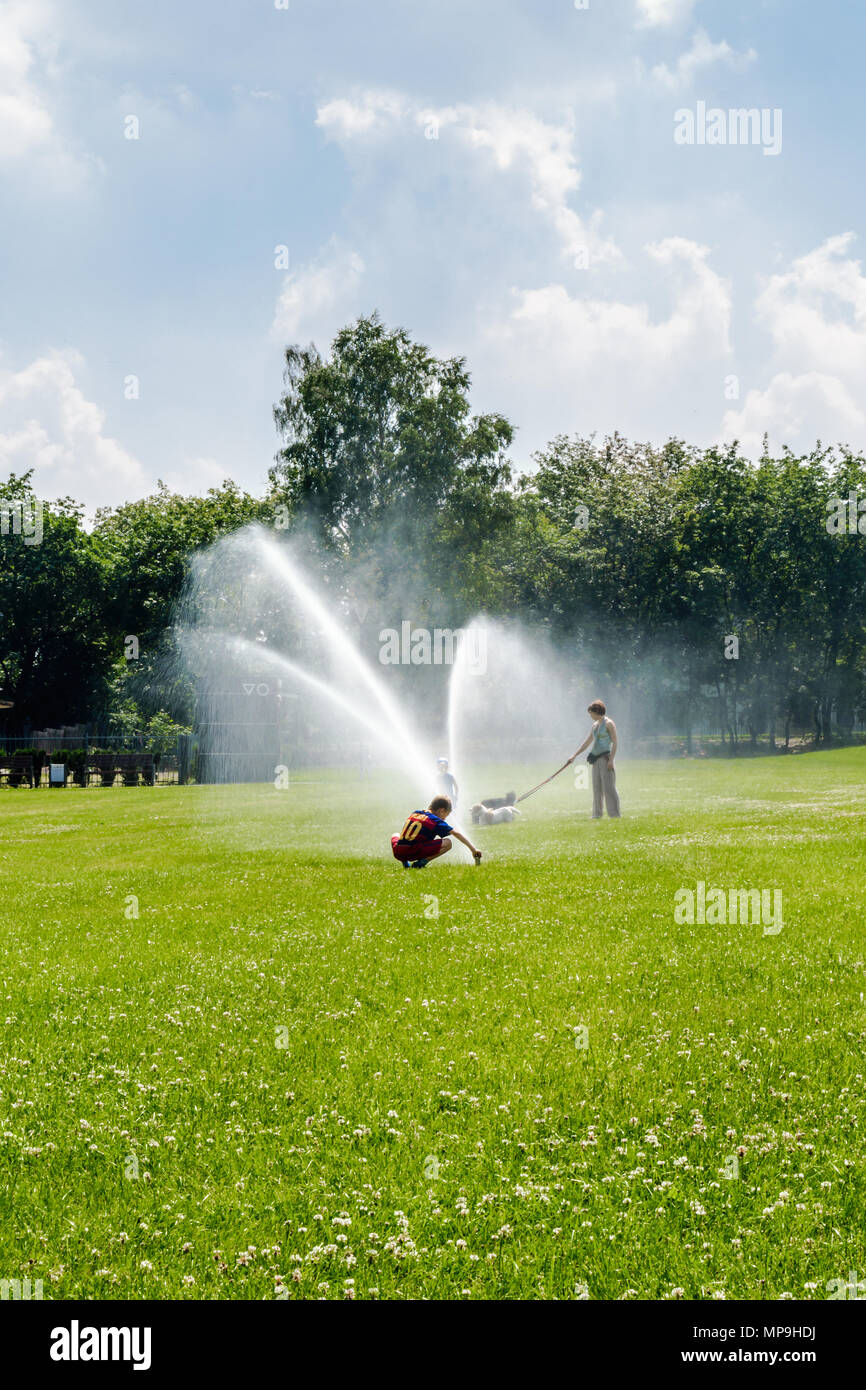 A little boy wearing football outfit playing with a water sprinkler in public park in Gliwice, Silesian Upland, Poland. - Stock Image