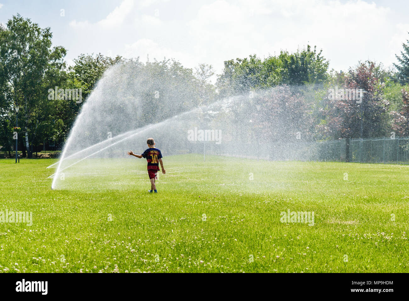 A little boy in football outfit is sprayed by water sprinklers in public park in Gliwice, Silesian Upland, Poland. - Stock Image