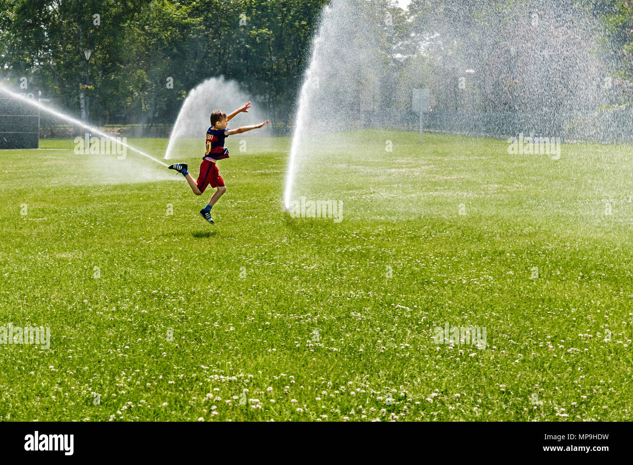 A little boy in a FC Barcelona football outfit jumping towards a cascade of water in the public park in Gliwice, Silesian Upland, Poland. - Stock Image