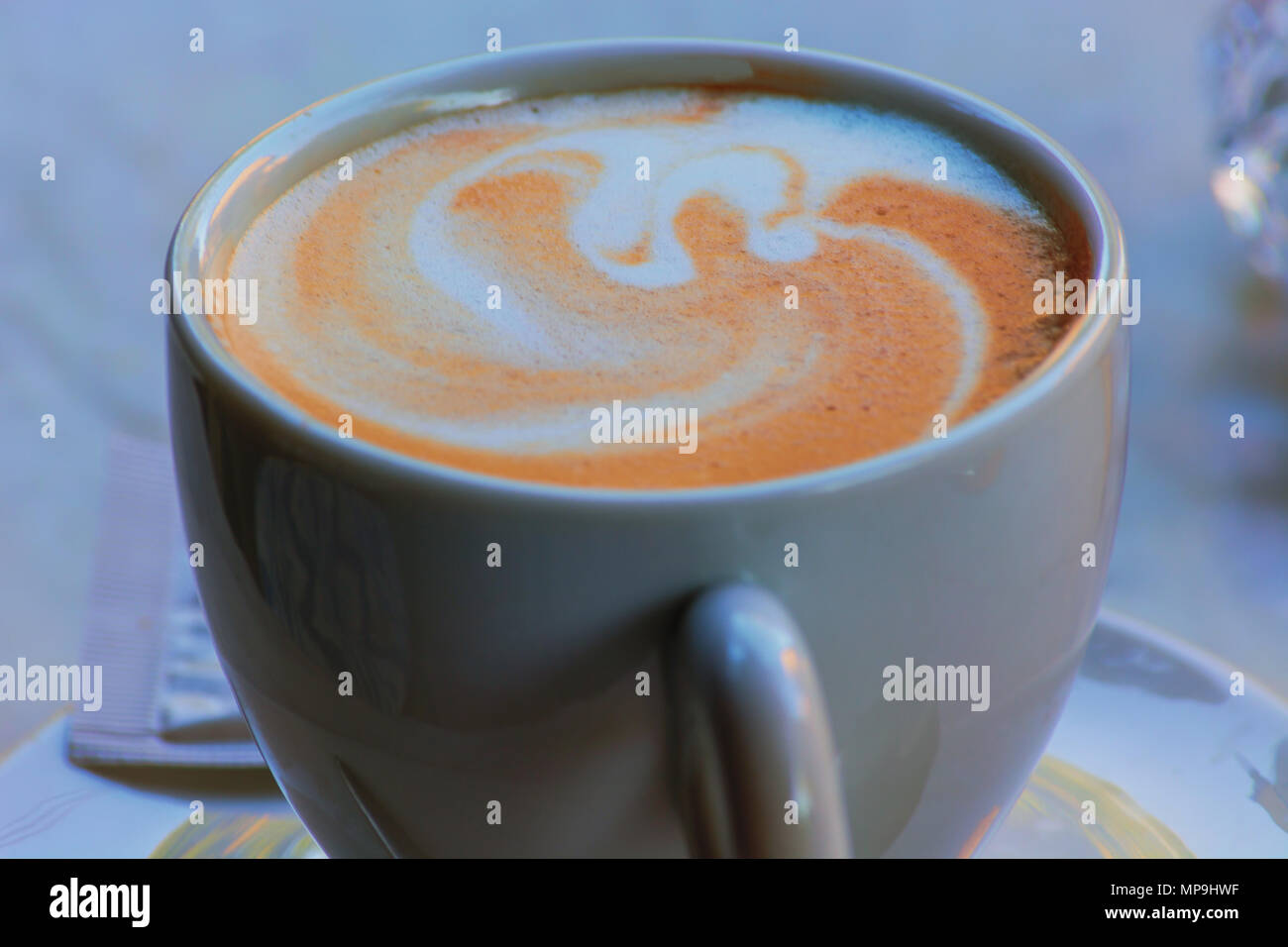 A white cup of coffee latte art before bokeh background - Stock Image