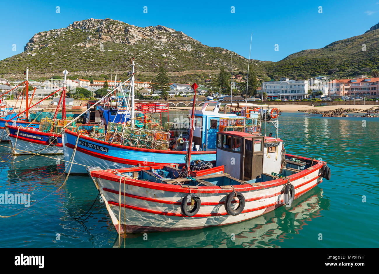 Fishing boats in the harbor of Kalk Bay with the Table Mountain range in the background near Cape Town, Western Cape Province, South Africa. - Stock Image