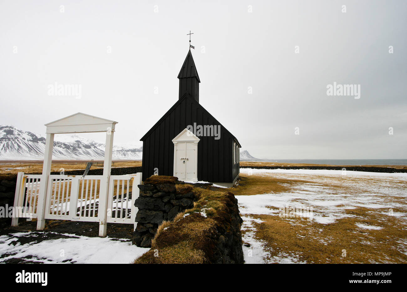 Gate and black wooden church of Budir in Iceland - Stock Image