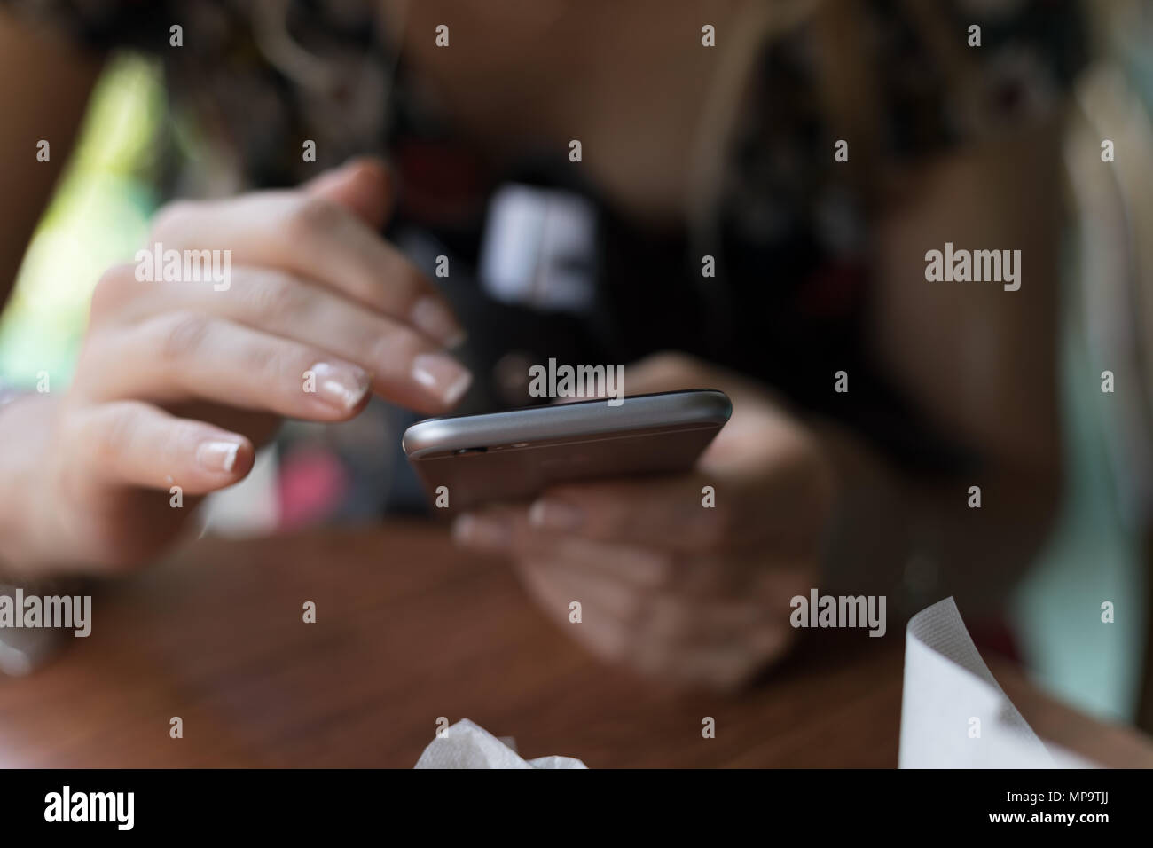 Girl hands holding mobile smart phone and dialing and digiting on the screen. - Stock Image