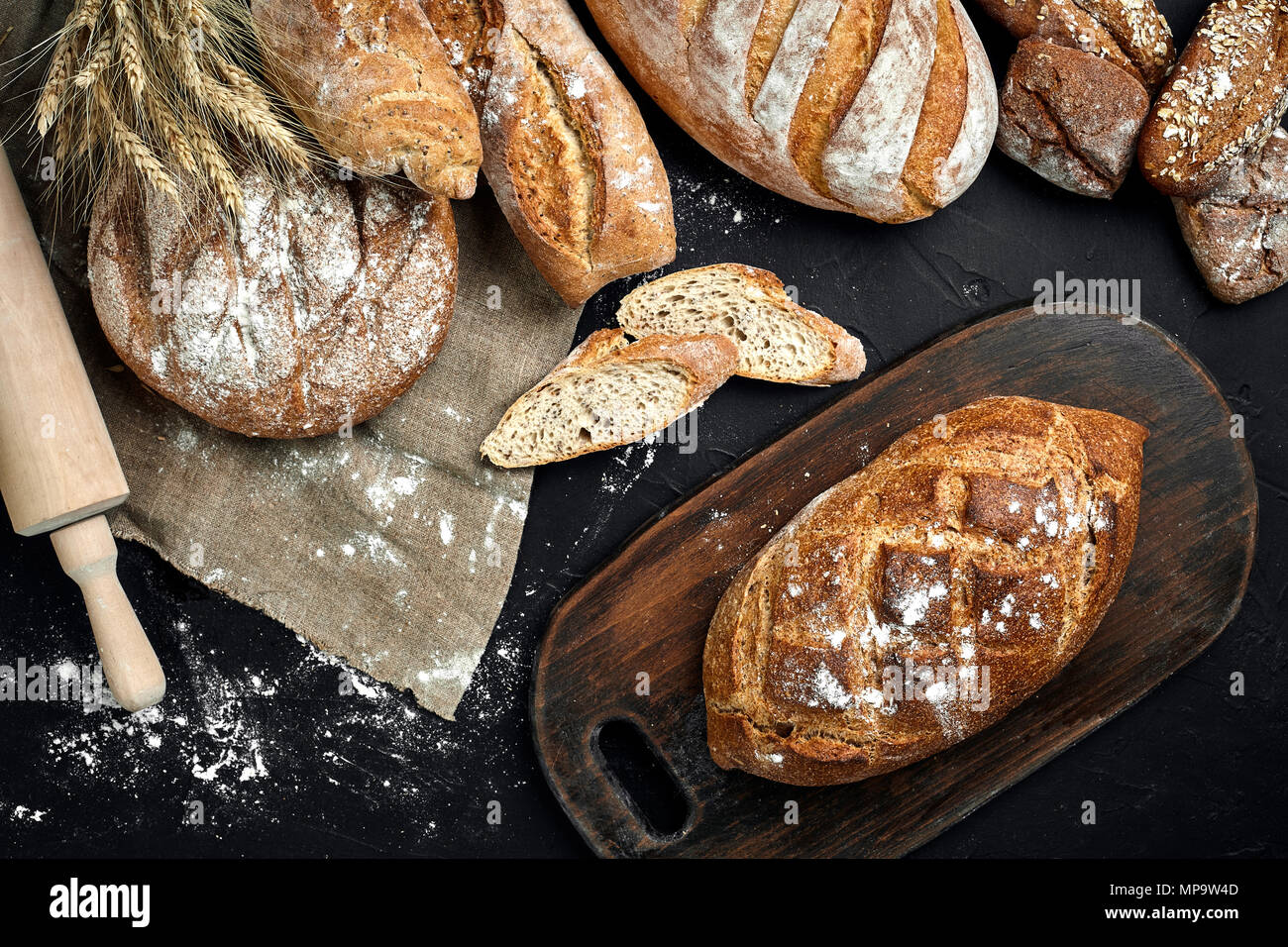 Fresh bread, wooden board and cutting knife on black table - Stock Image
