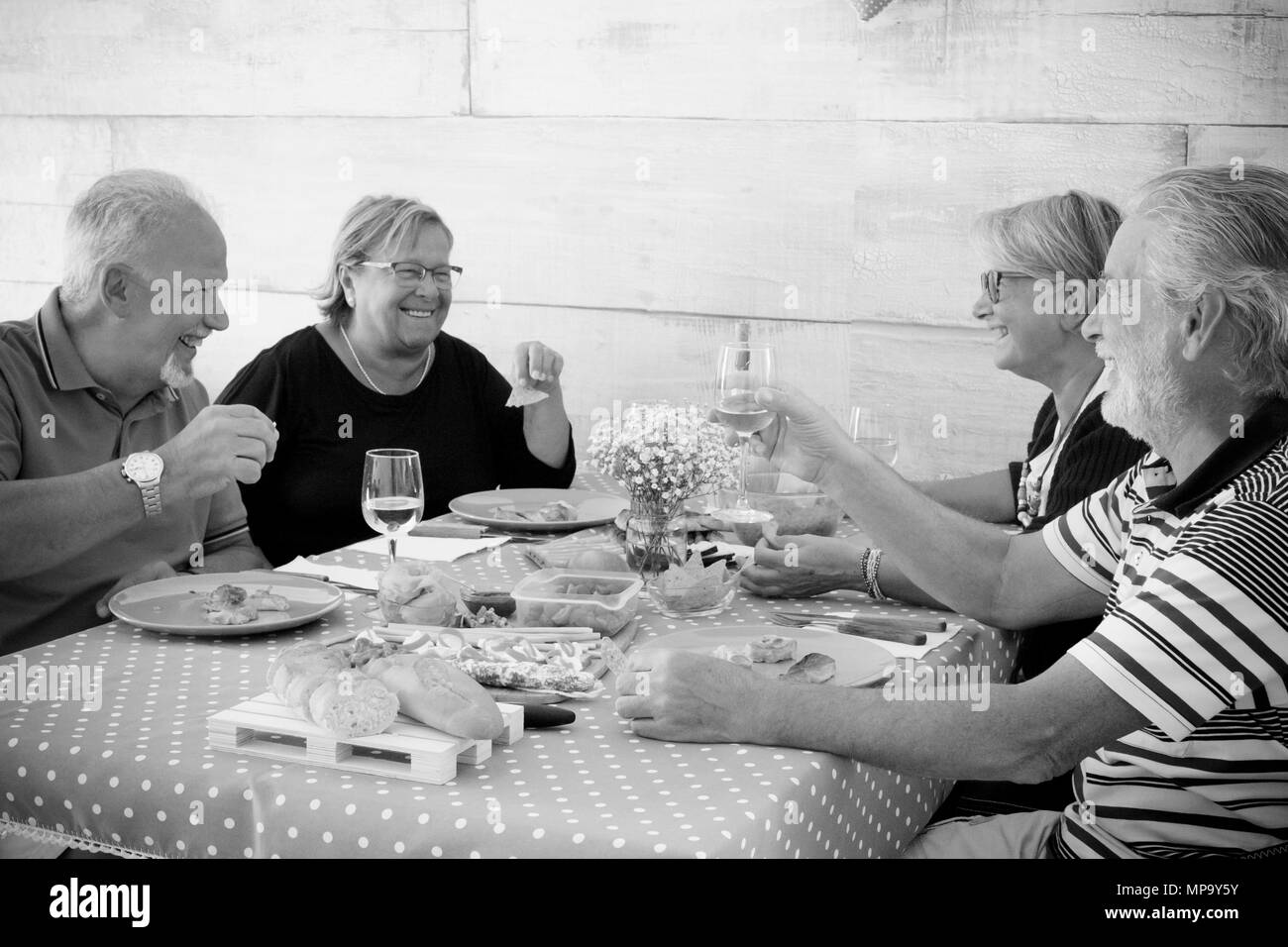home scene for a group of senior in black and white. Eating and laughing together with cups of wine and food. nice time with people and tasty things o - Stock Image