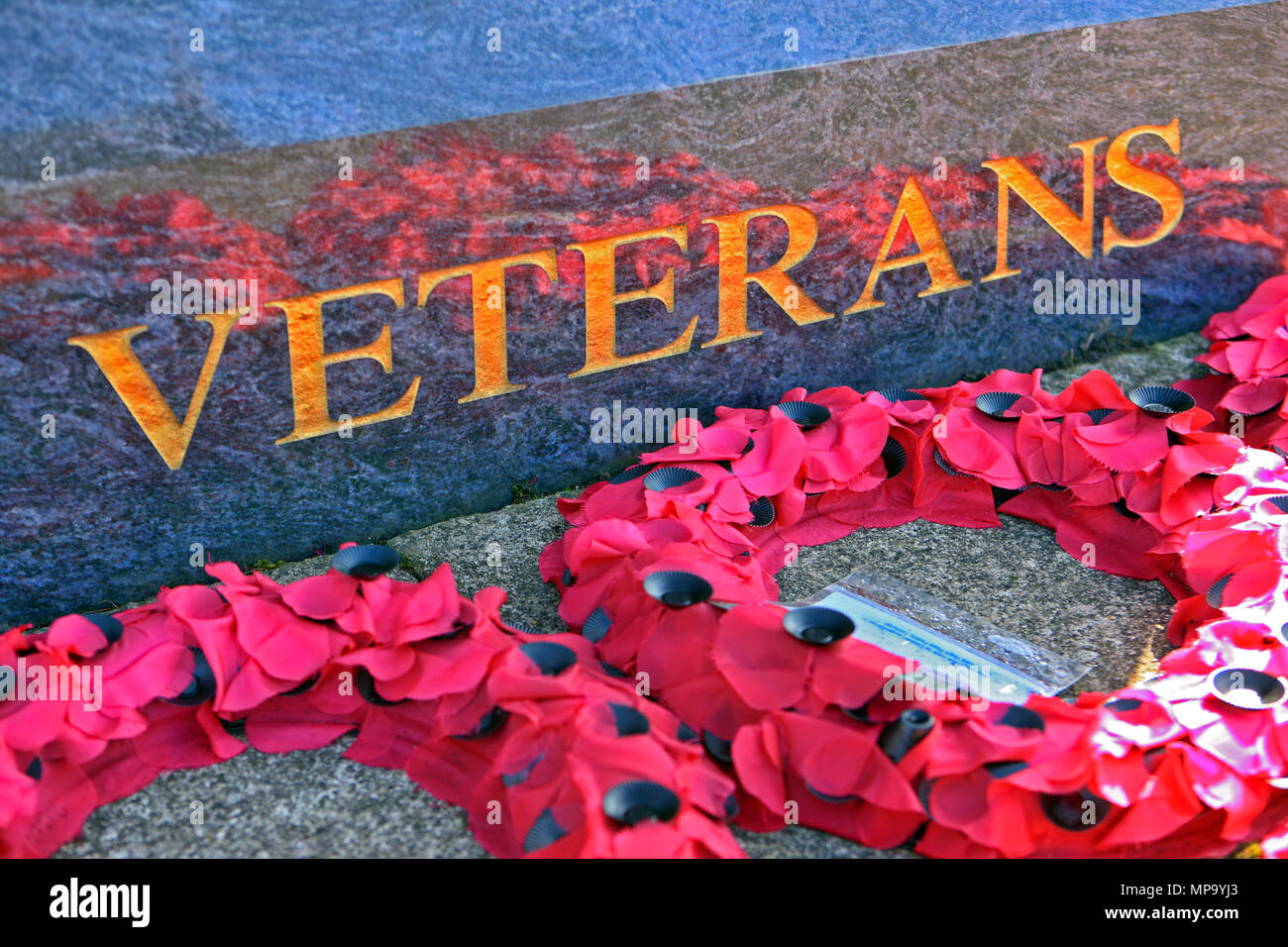 Poopy Wreaths at the foot of a memorial commemorating veterans of the armed forces, Glasgow, Scotland - Stock Image