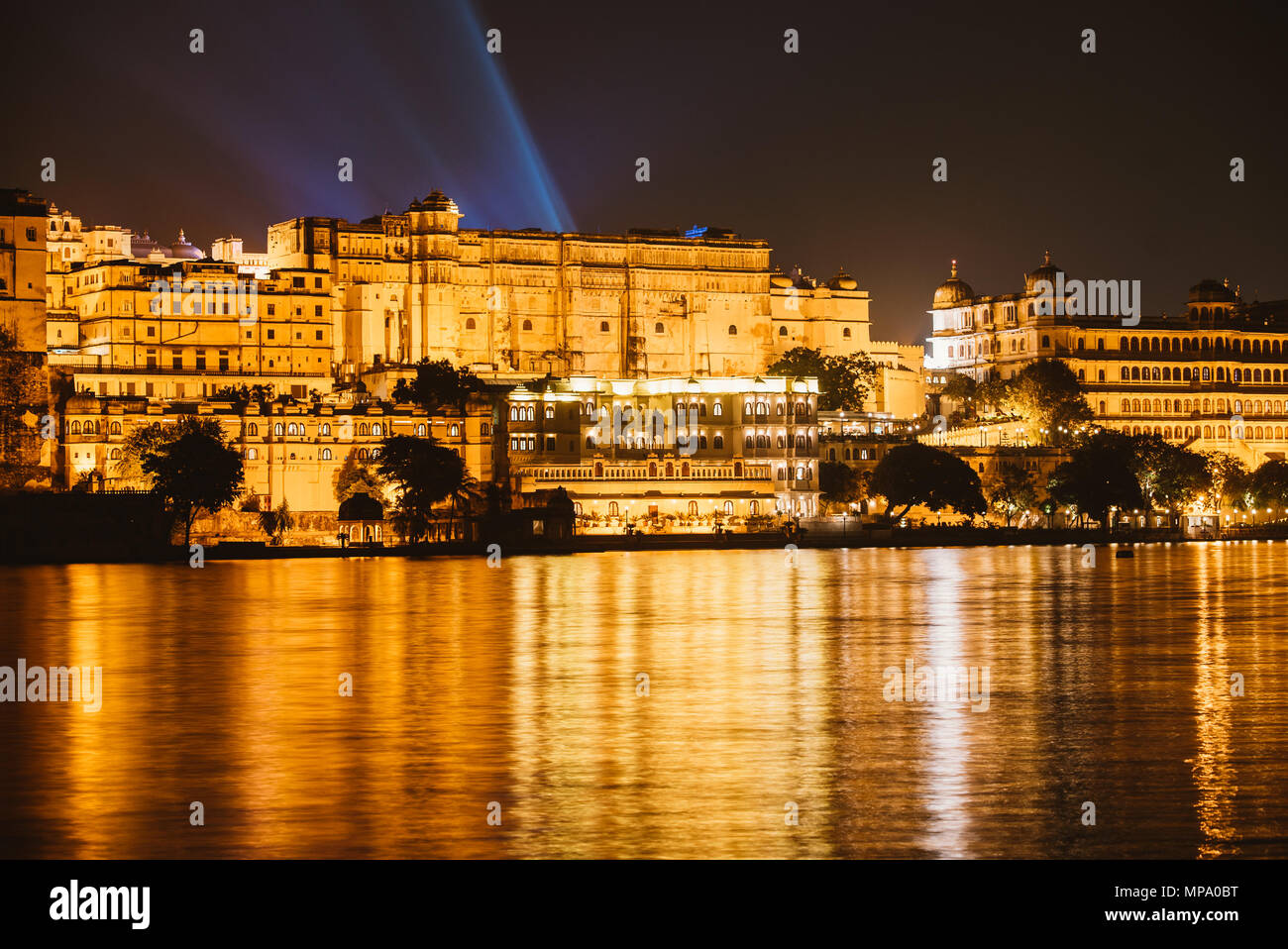 View of the city palace at night from the water in Udaipur, India - Stock Image