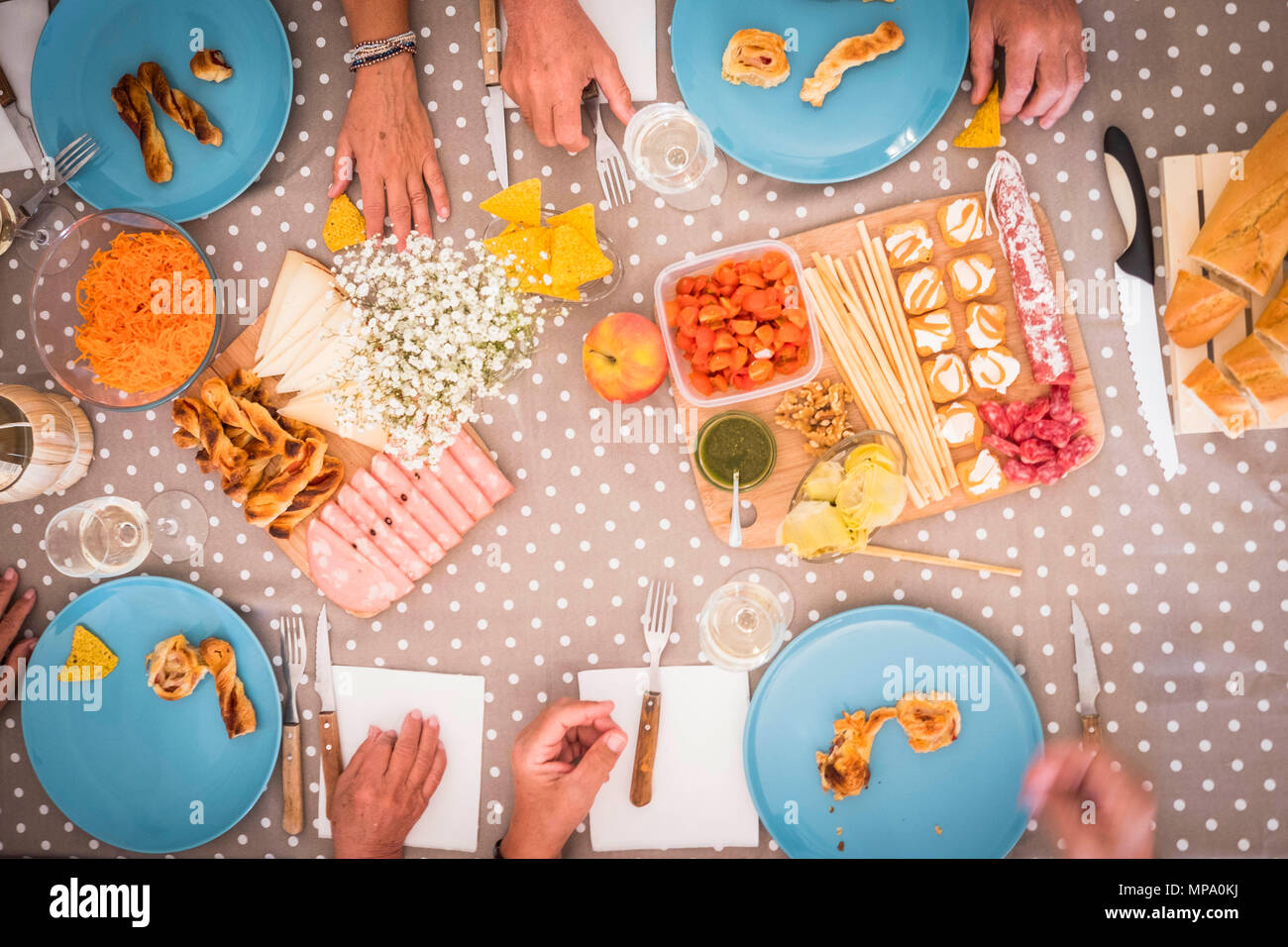 highview of a table during a lunch for 4 senior men and women. bright image with food like mortadella, carrots, slami, bread and more.many hands on th - Stock Image