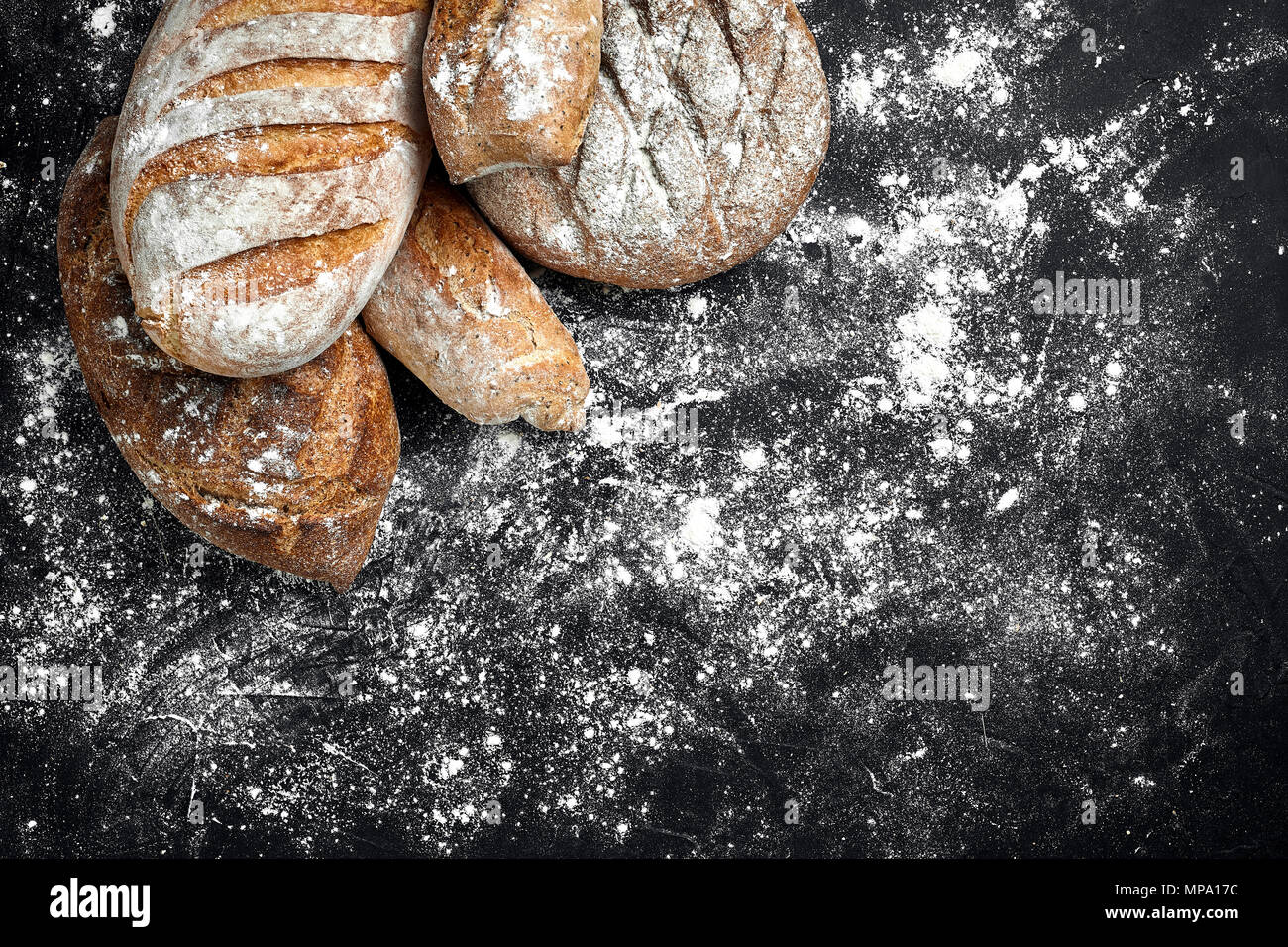 Mixed breads on black table. Top view with copy space. - Stock Image