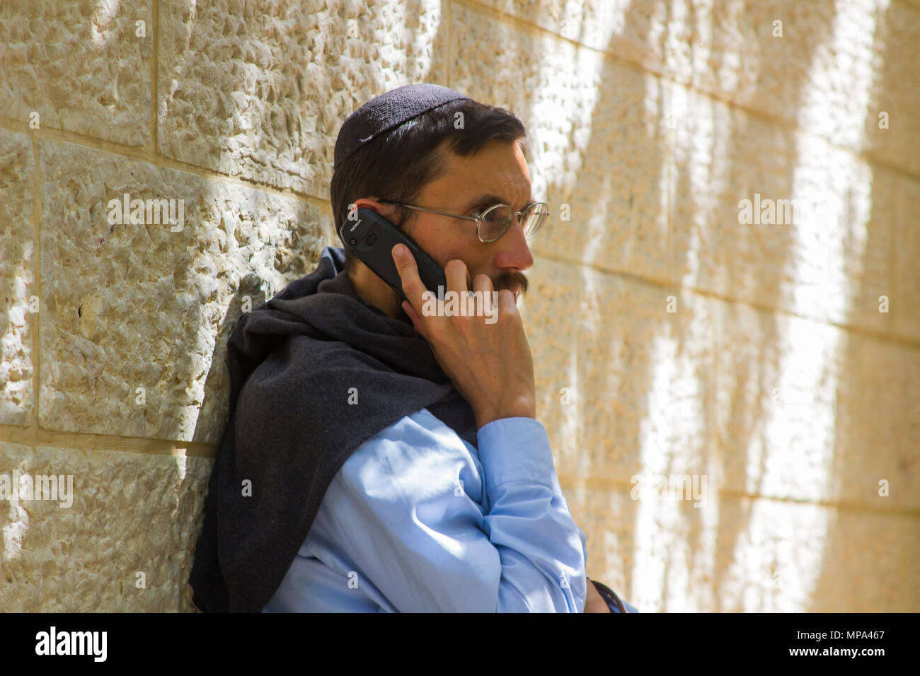 A young Jewish male with a moustache  using a mobile phone while leaning against a stone wall in Jerusalem Israel - Stock Image