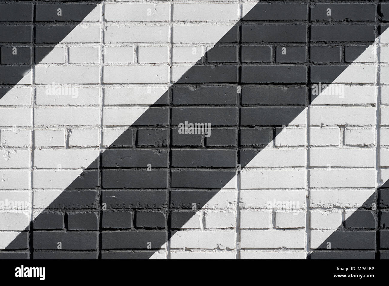 Painted diagonally bricks surface of wall in black and white color, as graffiti. Graphic grunge texture of wall. Abstract modern background - Stock Image