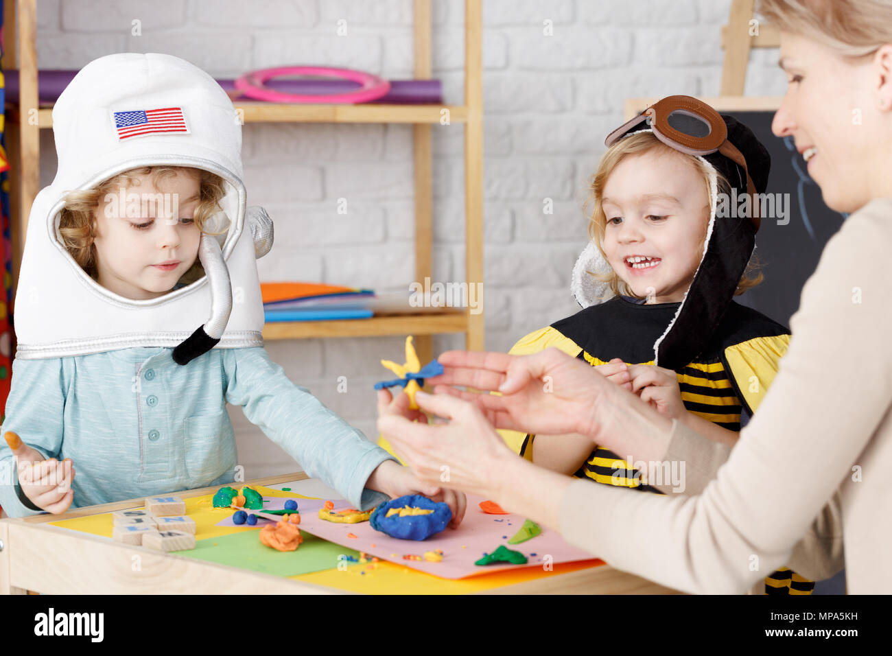 Little boy and girl dressed up on costume party in kindergarten - Stock Image
