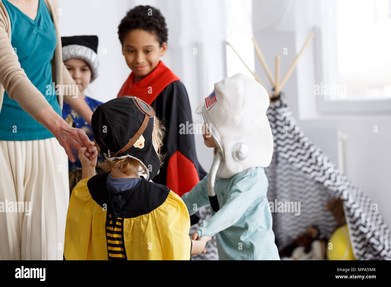 Group of children in costumes dancing in a circle - Stock Image