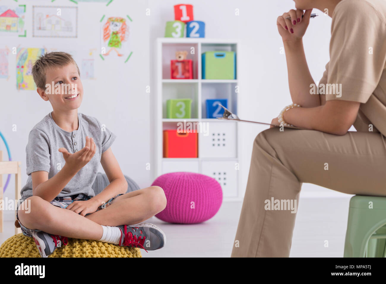 Shot of a smiling young boy talking to his psychologist - Stock Image