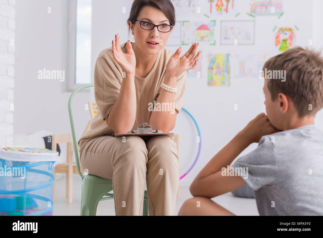Shot of a young psychologist having a session with a small boy - Stock Image