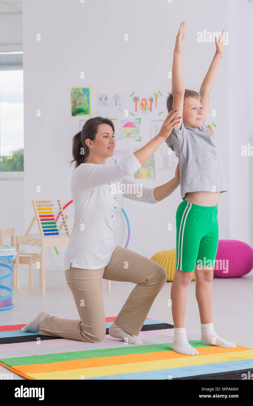 Shot of a little boy doing exercises with his physiotherapist - Stock Image