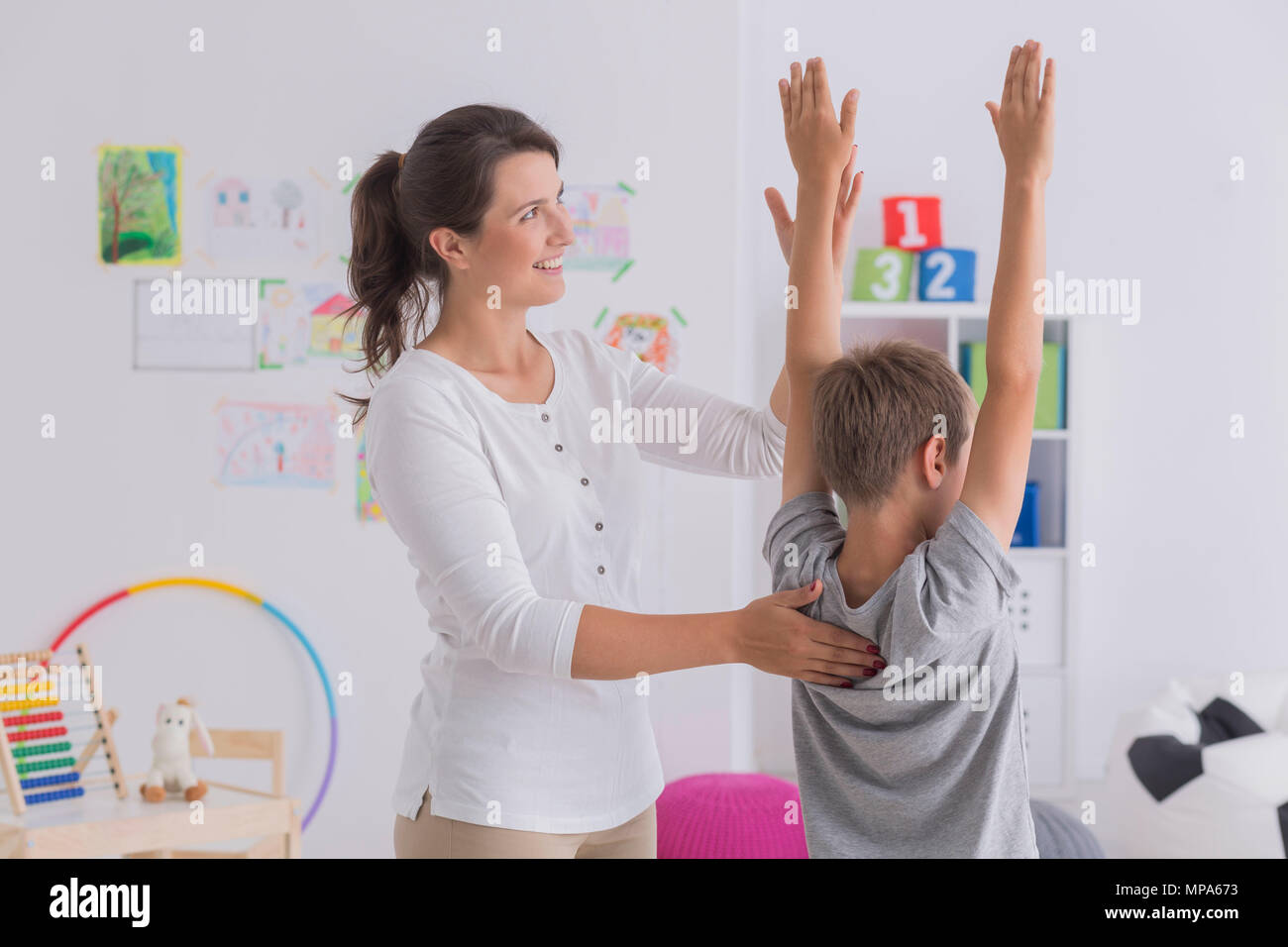Shot of a friendly physiotherapist exercising with her little patient - Stock Image