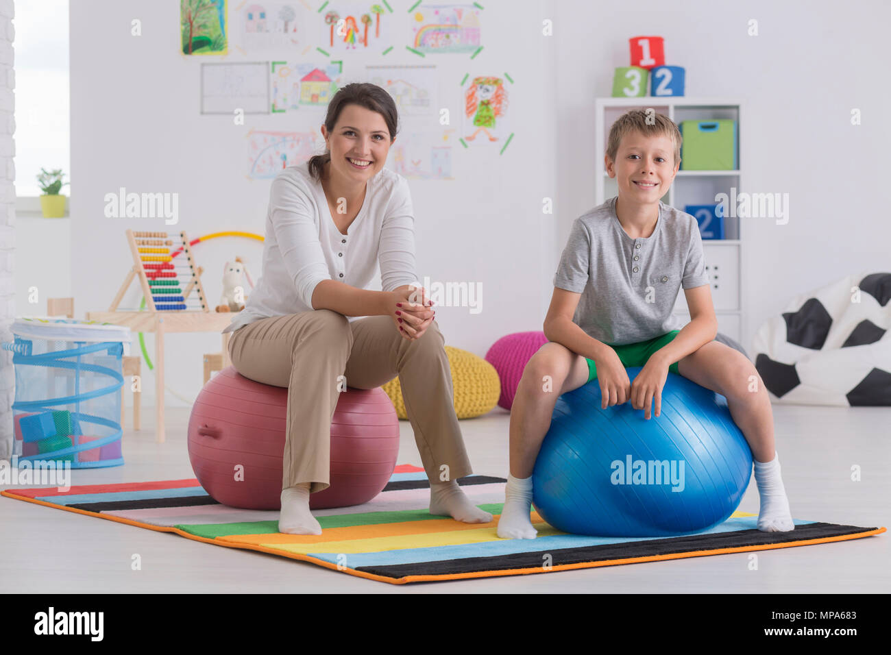 Shot of a young woman and a little boy sitting on exercise balls in a room - Stock Image