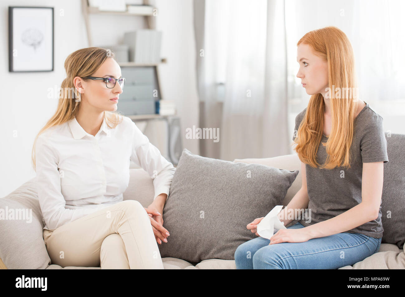Mental health concept - young psychologist listening to female patient on a sofa - Stock Image