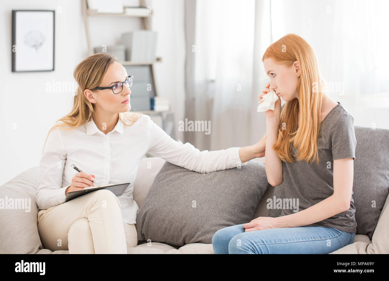 Medical concept - female psychologist comforting teenage girl with anxiety disorder - Stock Image