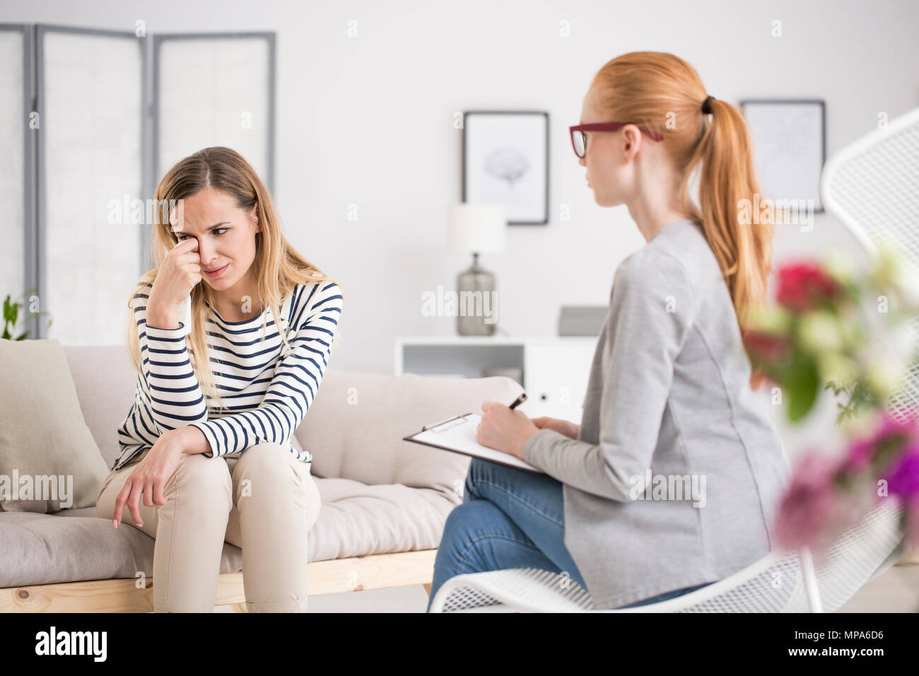 Unhappy woman suffering from depression crying during session at psychologist's office - Stock Image