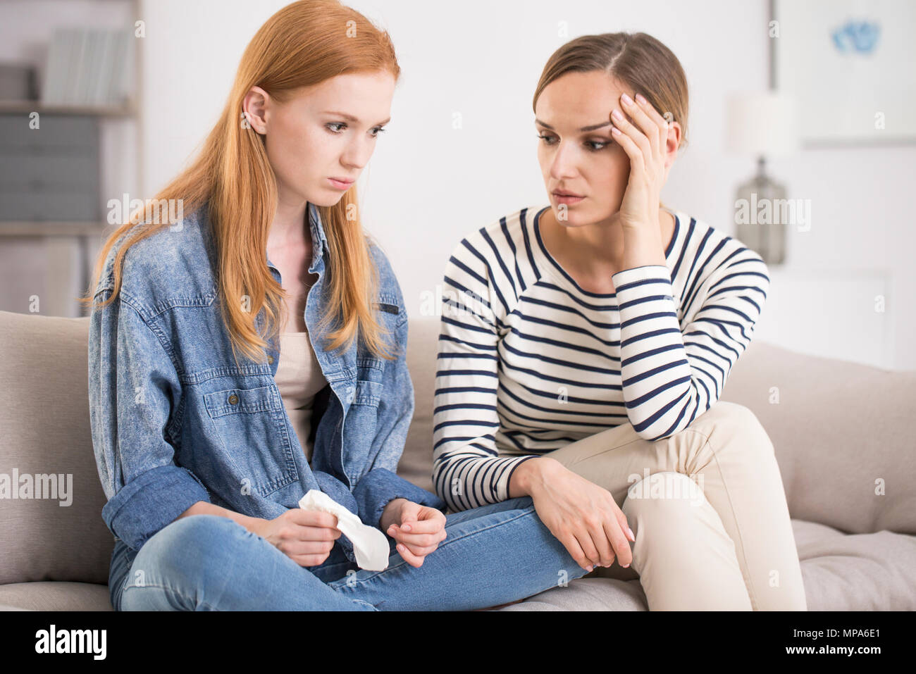 Young woman comforting her sad depressed sister while sitting on sofa in living room, concept of sister support - Stock Image
