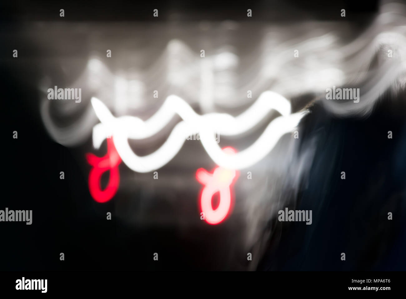 Abstract graphic resource background of black, white and red lines bokeh light trails in tunnel of dark evening road - Stock Image