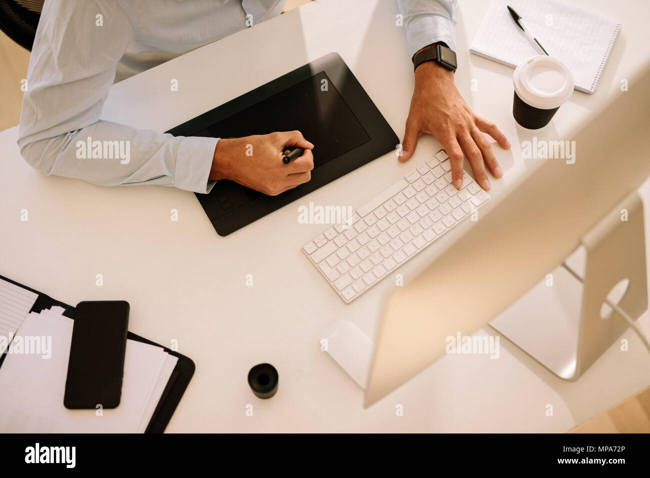 Top view of a man writing on digitizer with a computer in front. Man working on computer with a coffee cup on the table. - Stock Image