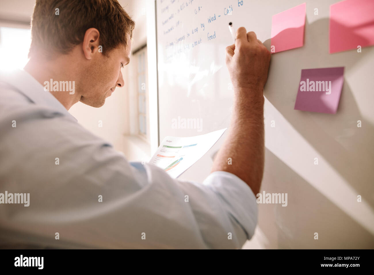 Entrepreneur making notes on a board and placing colorful sticky notes on the board. - Stock Image