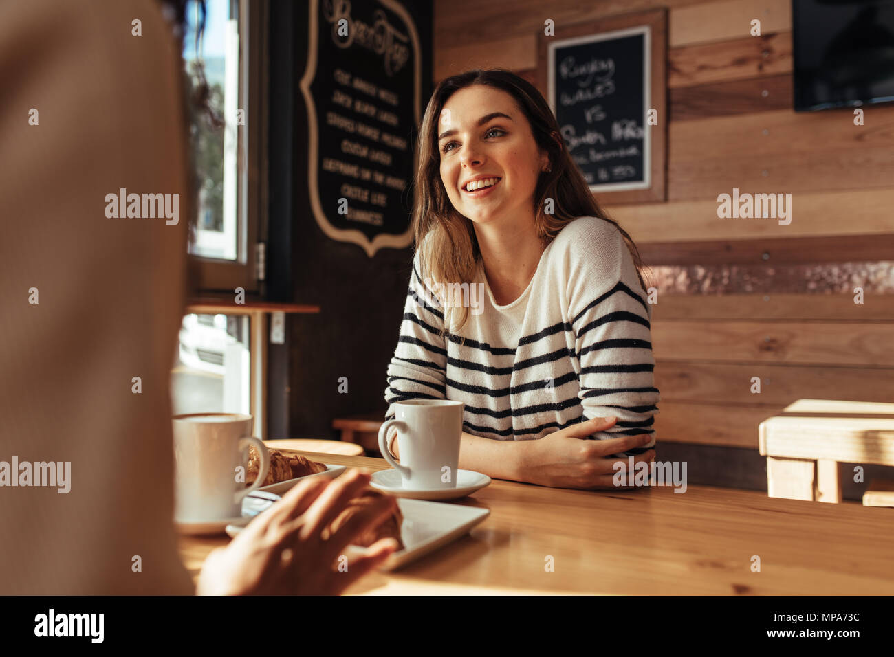 Smiling woman sitting in a restaurant talking to her friend. Friends sitting at a cafe with coffee and snacks on the table. - Stock Image