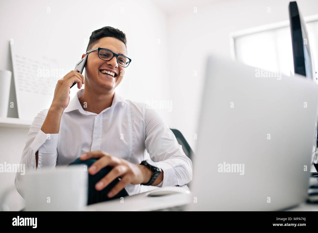 Smiling software developer talking over mobile phone sitting at his office desk with a laptop and coffee cup in front. Man wearing spectacles working  - Stock Image