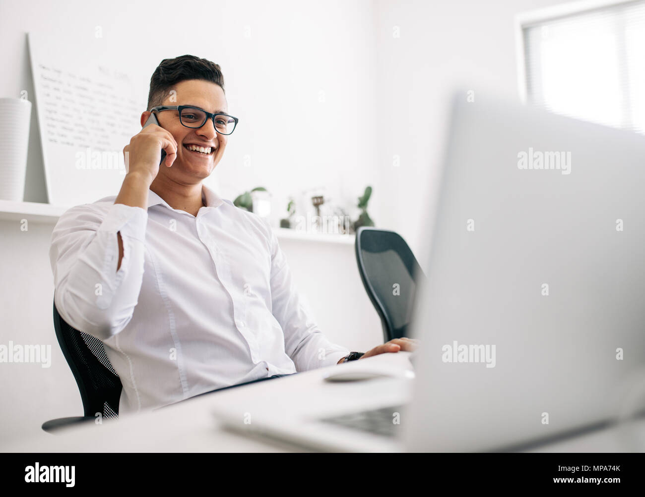 Smiling software developer talking over mobile phone sitting at his office desk with a laptop in front. Man wearing spectacles working on laptop compu - Stock Image