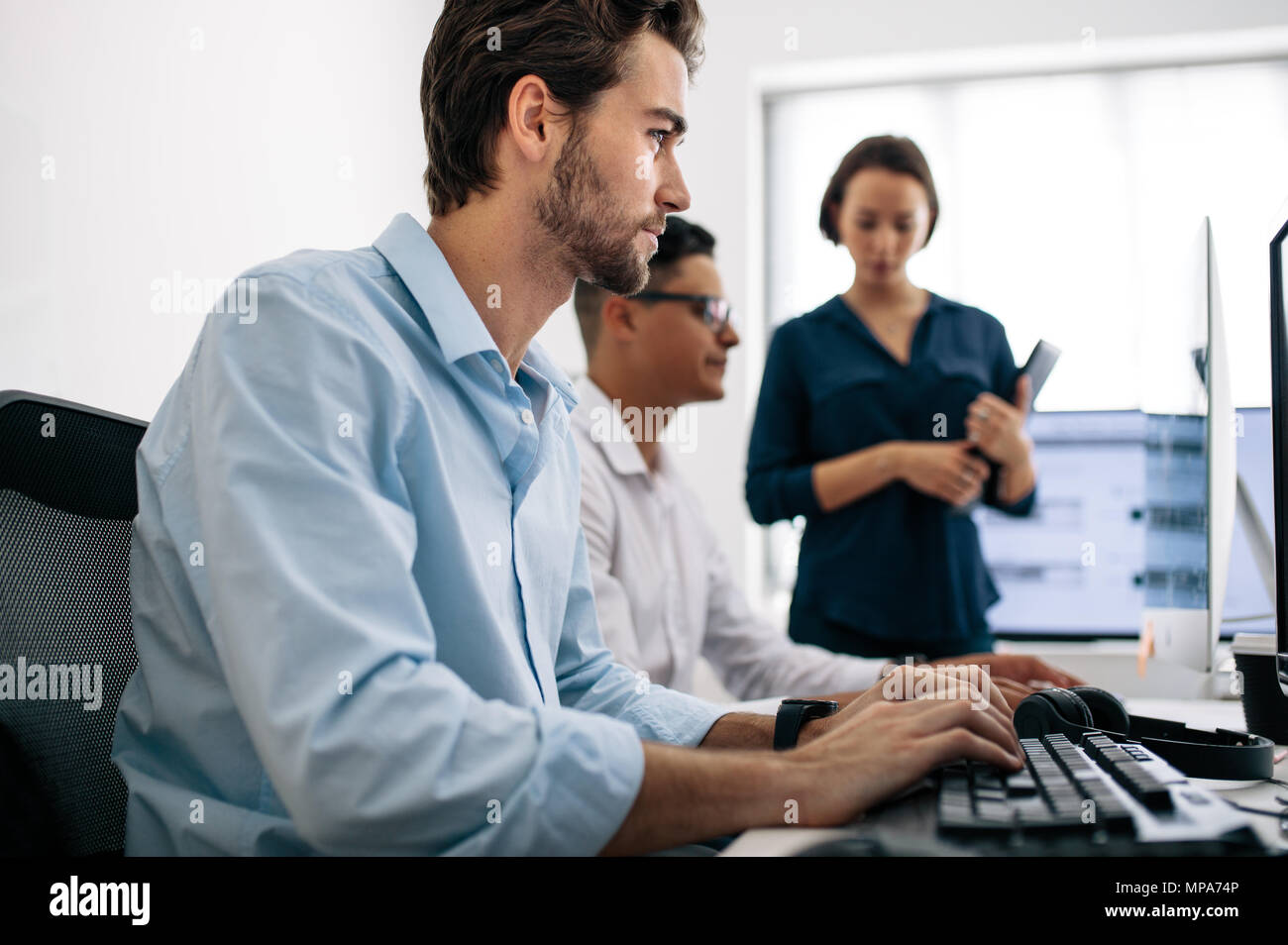 Software developers sitting at office working on computers. Two men developing applications on computer while a female colleague looks on. - Stock Image