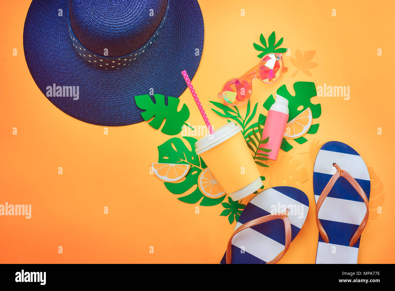 Summer vacation flat lay with tropical leaves, a refreshing drink, sunglasses, sunscreen, flip-flops, hat on a sunny yellow background with copy space Stock Photo