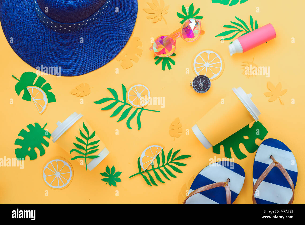 Summer vacation flat lay with tropical leaves, a refreshing drink, sunglasses, sunscreen, flip-flops, hat on a sunny yellow background with copy space - Stock Image