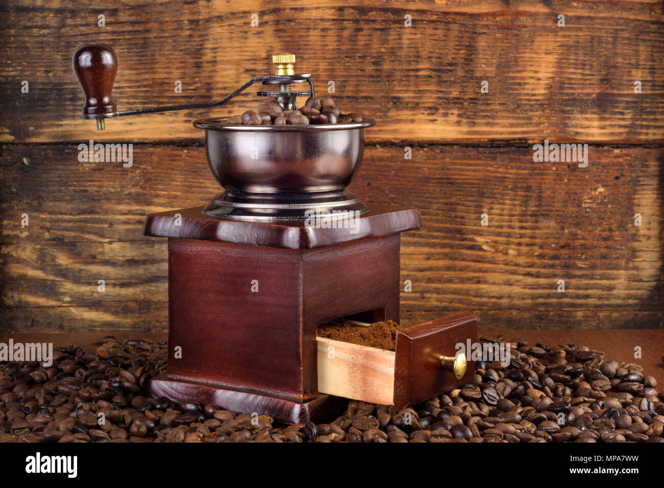 Traditional wooden coffee mill grinder with roasted coffee beans and wooden background. Retro and Vintage Food and drink concept Stock Photo