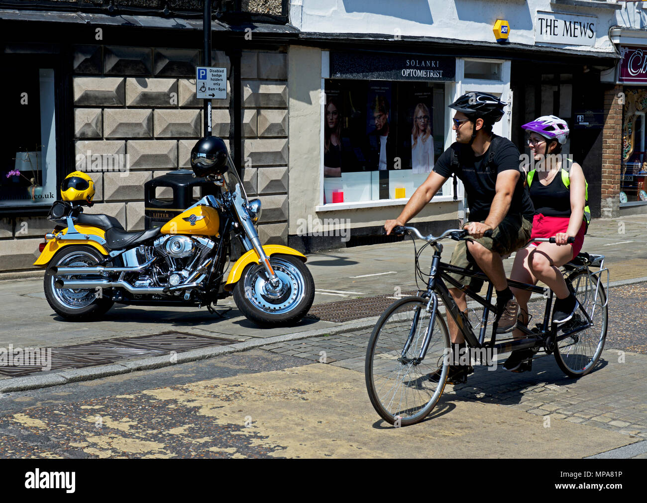 Couple riding tandem past Harley Davidson motorbike, St Ives, Cambridgeshire, England UK - Stock Image