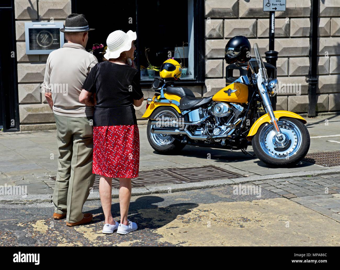 Senior couple admiring Harley Davidson motorbike, St Ives, Cambridgeshire, England UK - Stock Image