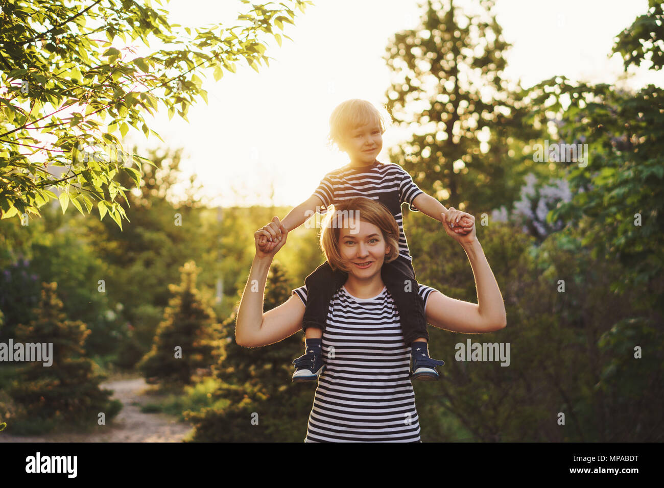 Mother and son in striped T-shirts. Woman is holding boy at piggieback. Family time together. Have fun - Stock Image