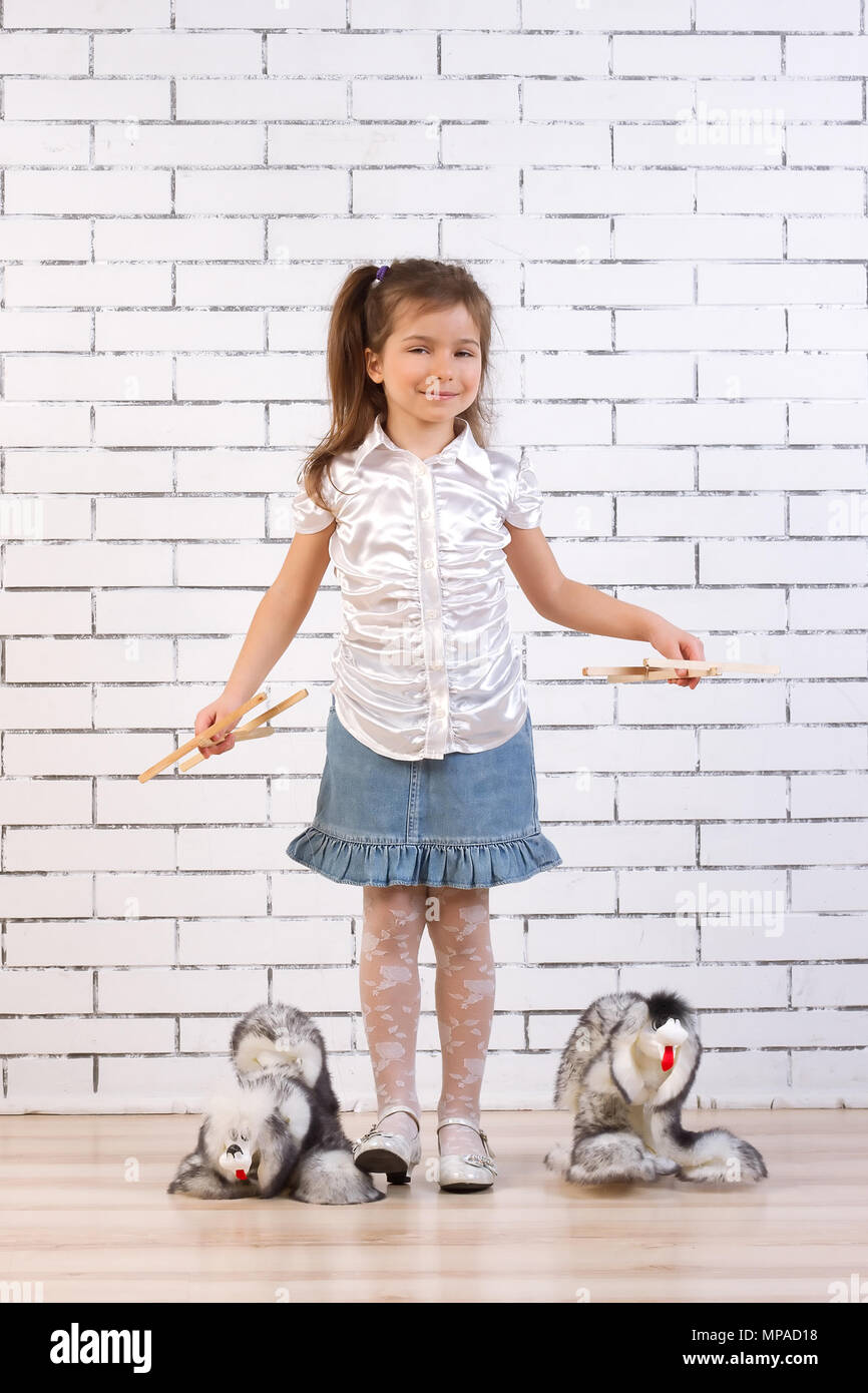 little girl walks two identical toy dogs - Stock Image