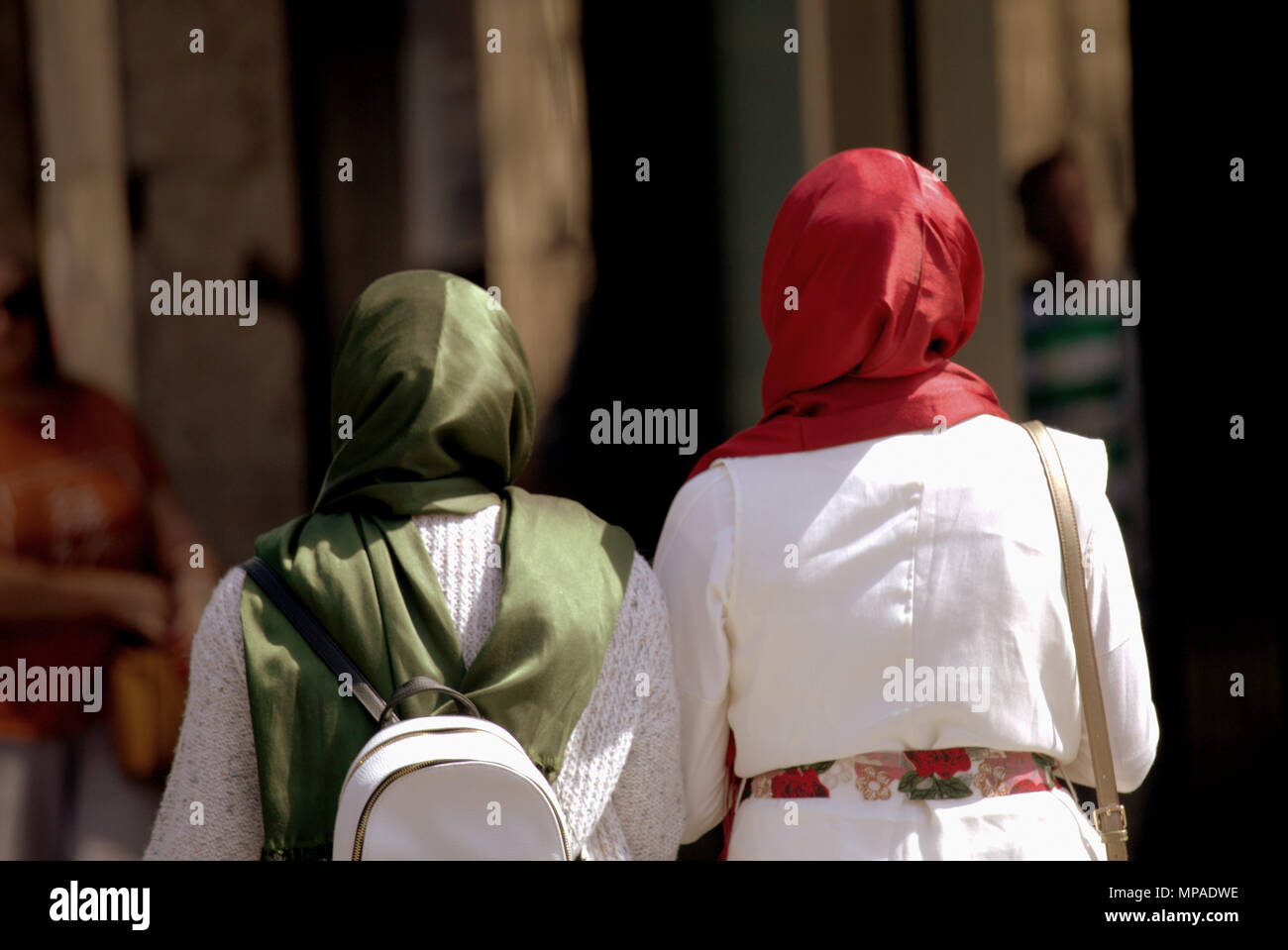 two  headscarfs headscarf headscarves hijab hijabs colors colours red and green on a sunny day Muslim Muslims on street graphic copyspace - Stock Image