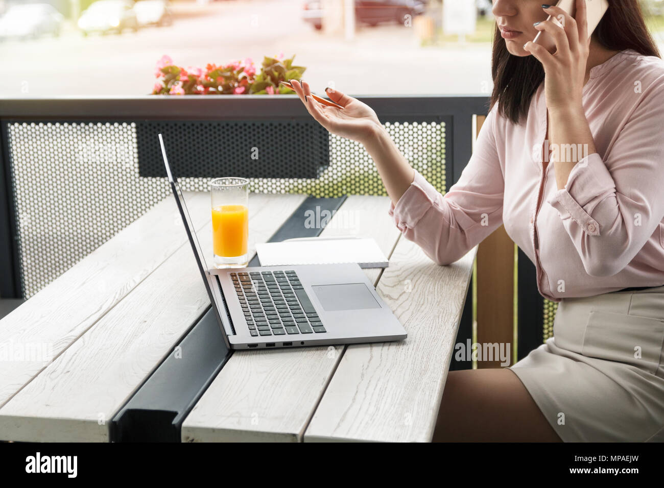 Young business woman speaking on the phone and gesticulating holding a pencil, laptop and juice on desk. - Stock Image